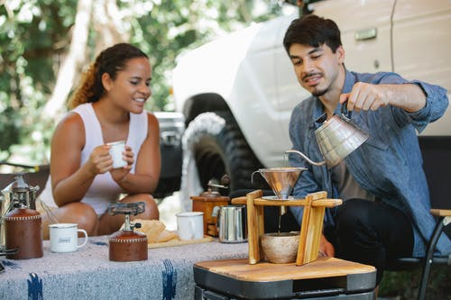 Cheerful young multiracial couple in casual clothes pouring boiling hot water into pour over filter while having coffee break together in sunny nature