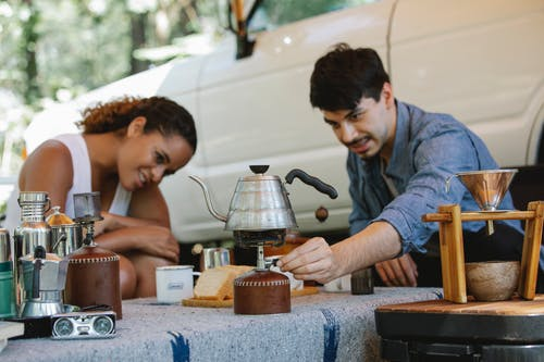 Diverse couple switching portable stove to boil water during picnic