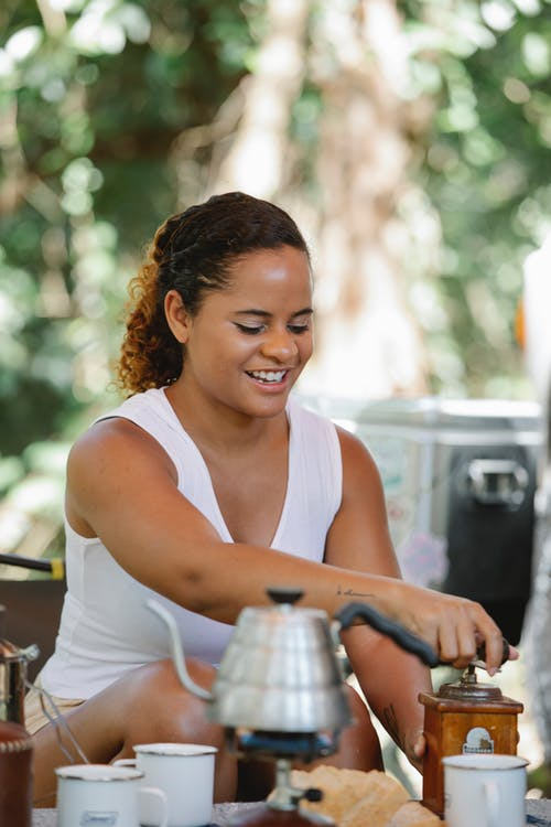 Happy young ethnic female tourist grinding coffee while sitting at table during picnic in nature