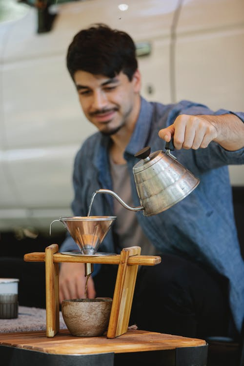 Happy young ethnic male tourist pouring water into cup through metal funnel while brewing coffee during picnic on sunny day