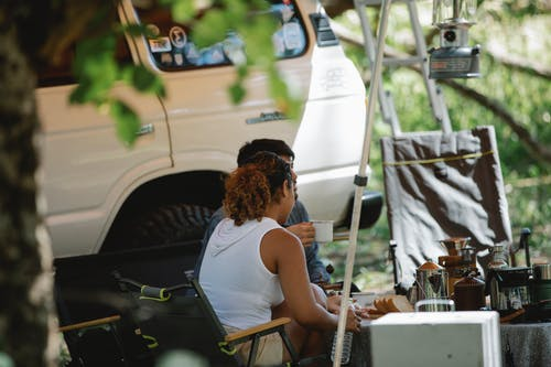Side view of unrecognizable couple sitting at table near SUV car and drinking coffee during road trip in nature on sunny summer day