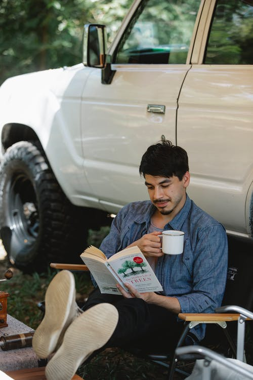 From above of relaxed young ethnic guy in casual outfit reading book and drinking coffee while sitting on chair near off road car during camping in sunlight