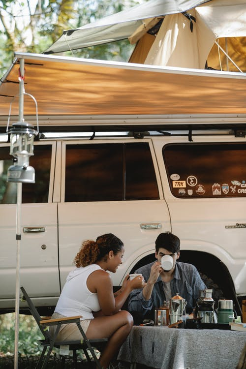 Anonymous diverse couple drinking coffee near off road vehicle in park