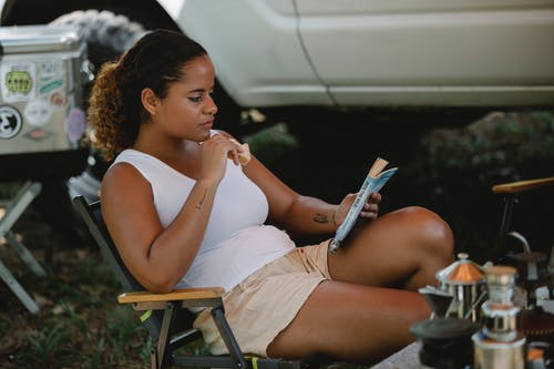 Thoughtful young ethnic woman eating toast and reading book at campsite