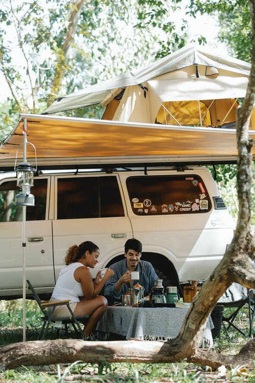 Cheerful young diverse couple having lunch under tent near off road car during camping in green forest on sunny summer day
