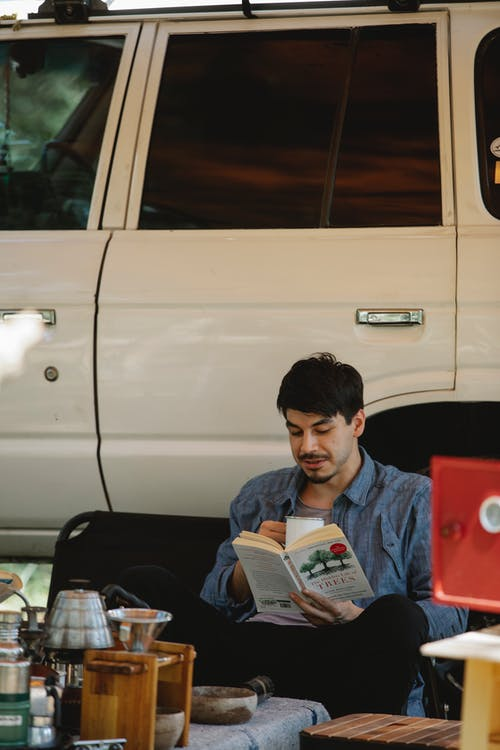 Relaxed young ethnic man reading book sitting near car at campsite