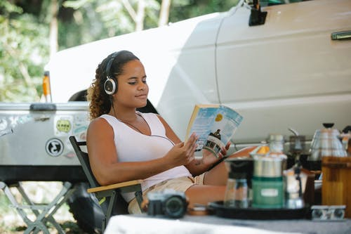 Content young ethnic woman listening to music and reading novel in nature