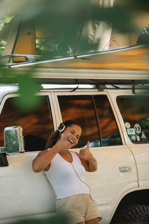 Excited young ethnic female camper showing thumbs up and listening to music in headphones while leaning on car under tent during summer holidays