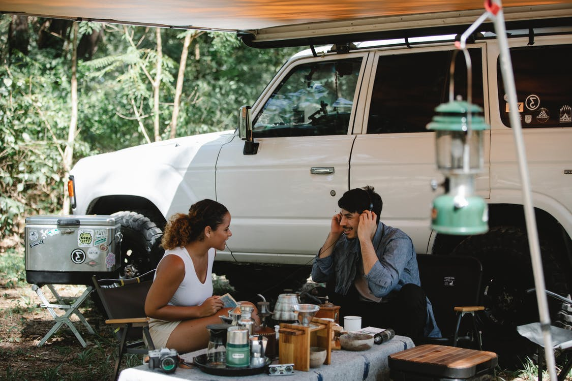 Cheerful multiracial couple communicating while sitting at table near camping van with awning in forest with green trees in sunny day
