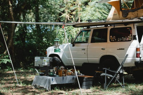 Camper offroader with roof top tent and awning camping in nature among green trees in sunny day