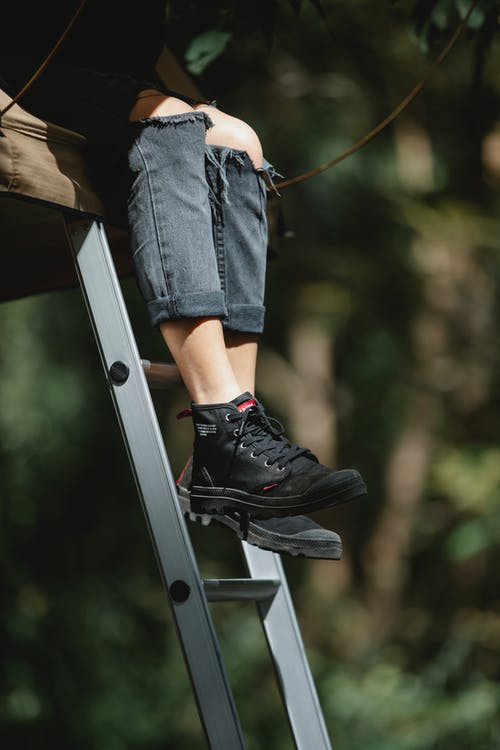 Person sitting on high ladder in park