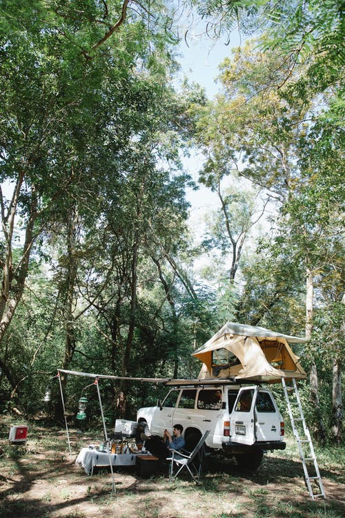 Camping car with tent on roof parked in forest in sunlight