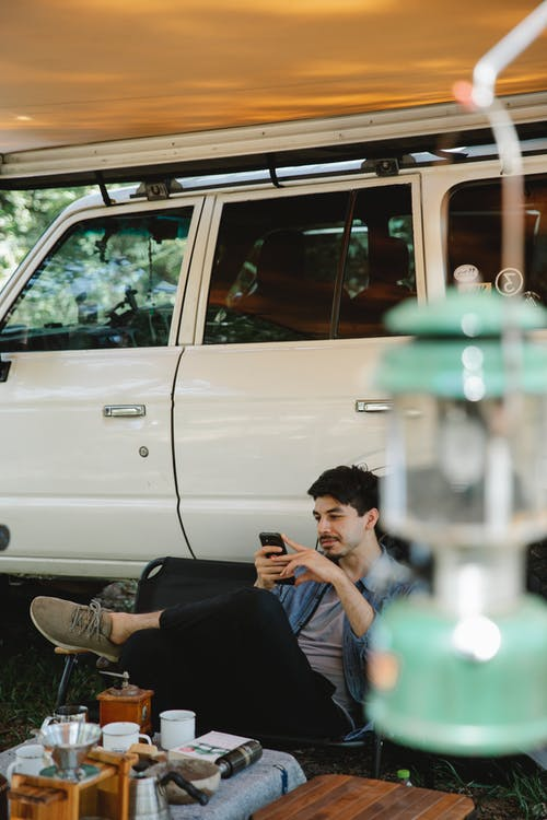Cheerful man traveler in casual clothes sitting on camp chair and using smartphone near camper offroader with awning placed in forest in sunny day
