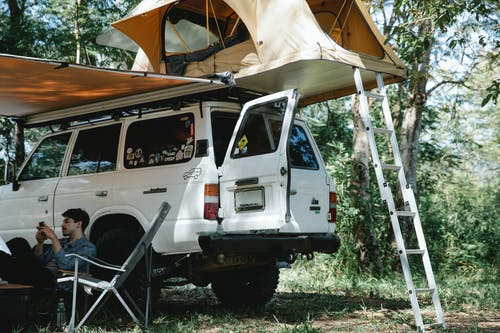 Man sitting under awning placed near offroader with tent on roof in forest