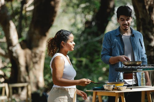 Focused multiethnic couple cooking on metal stove using skillet and spatula in woods