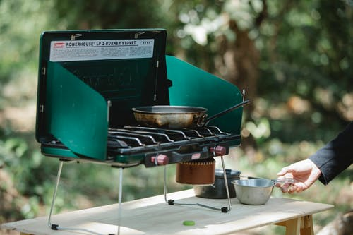 Crop man cooking on metal stove in nature