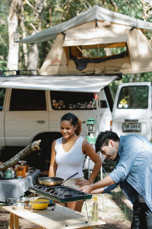 Content diverse couple cooking in camp