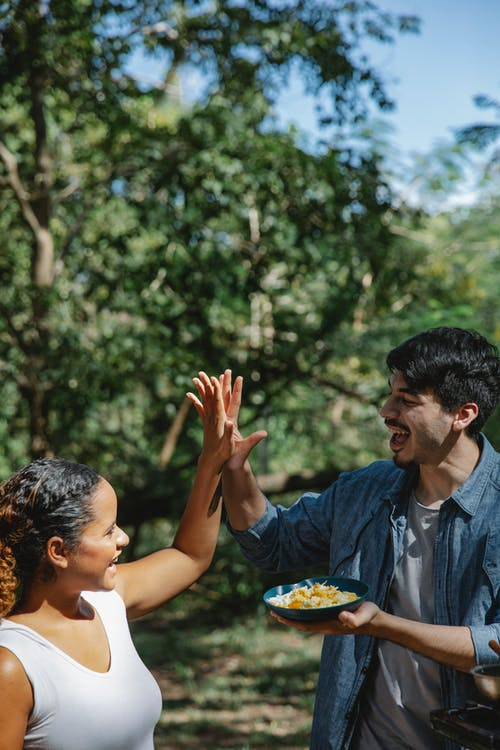 Cheerful young multiracial couple in casual outfits with plate of scrambled eggs in forest giving each other high five