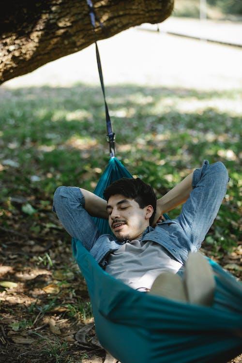 Relaxed man lying in hammock in forest