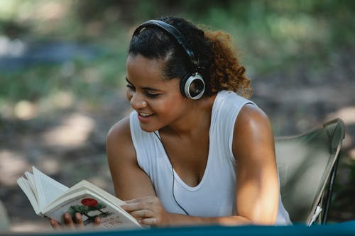Cheerful young Hispanic female in white tank top listening to music via headphones and reading book while sitting on chair in park