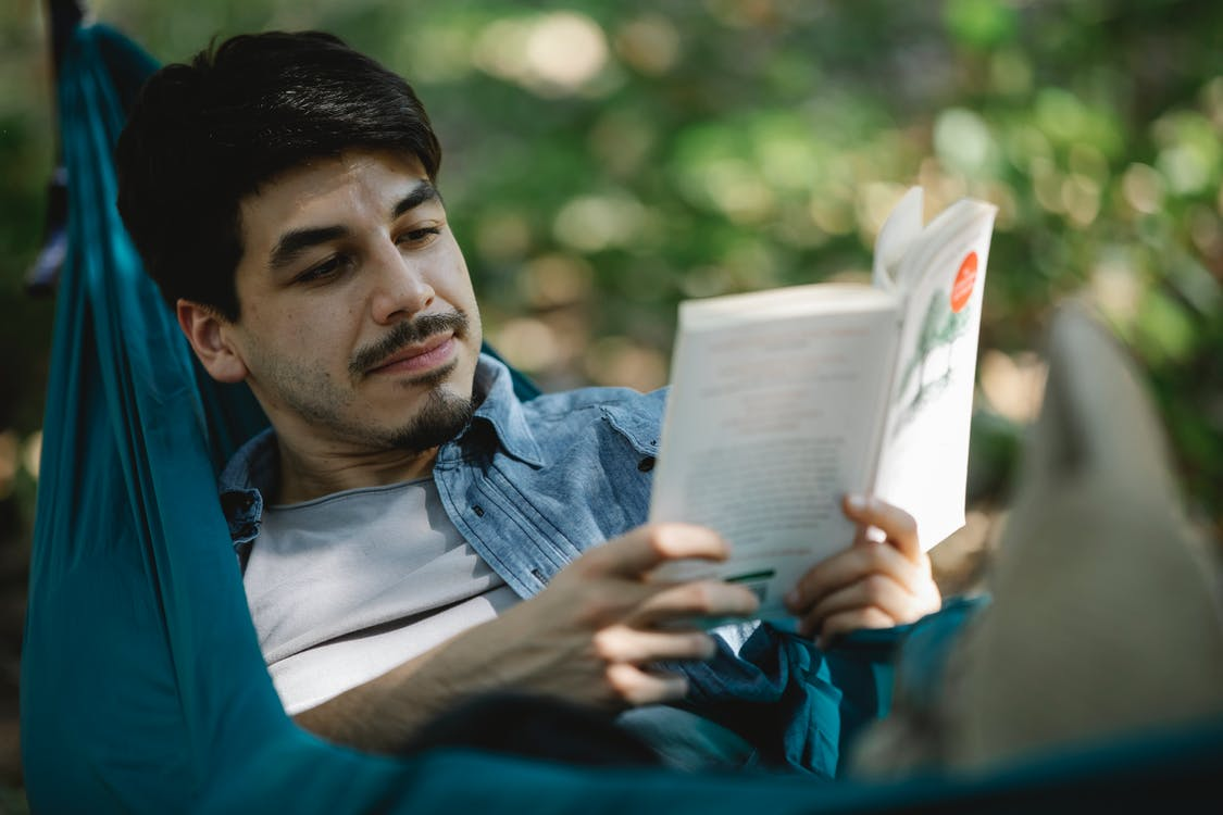 Focused bearded man with book on hammock