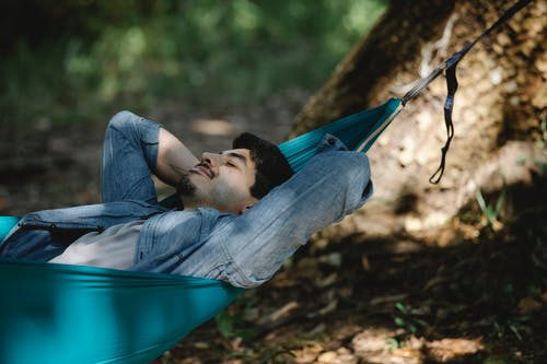Dreamy man resting in hammock in woods