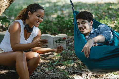 Positive multiethnic couple laughing at funny moment in book