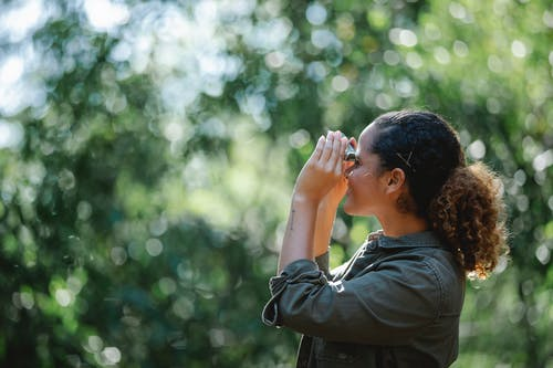 Delighted ethnic woman looking at binocular