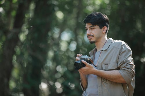 Focused bearded young male photographer in casual shirt with photo camera standing in woods and looking away