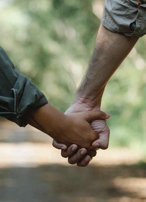 Crop couple holding hands walking in park