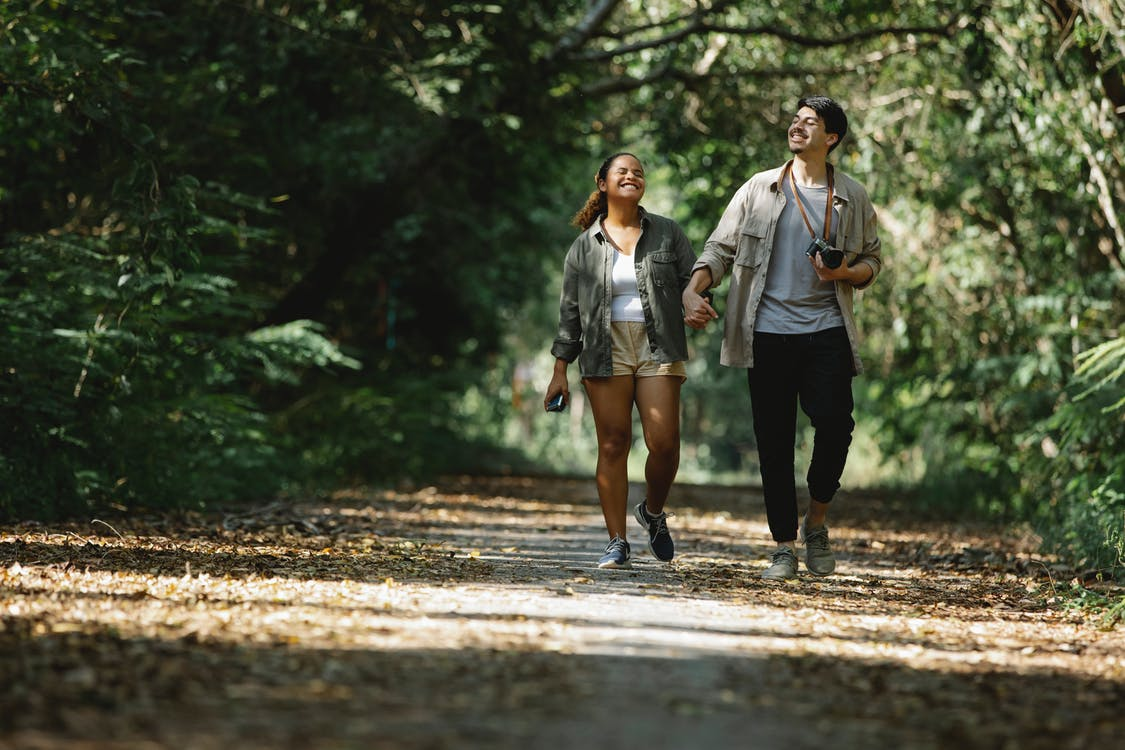 Smiling diverse couple holding hands walking in park