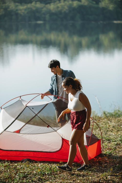 Young couple putting up tent on river bank