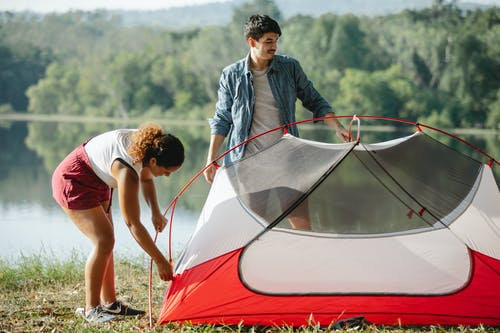 Traveling young couple putting up tent near river