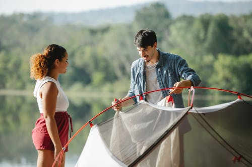 Focused young multiethnic traveling couple in casual clothes putting up tent together near lake in summer day