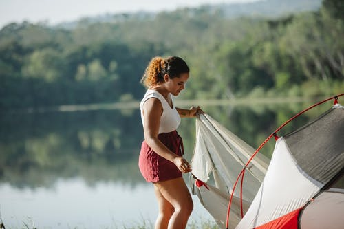Young tourist putting up tent near river