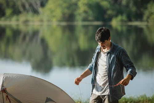 Concentrated young male traveler standing on bank of river and putting up tent in summer day against blurred background
