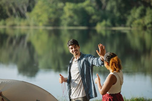 Happy young traveling couple giving each other high five while standing on river bank and putting up tent