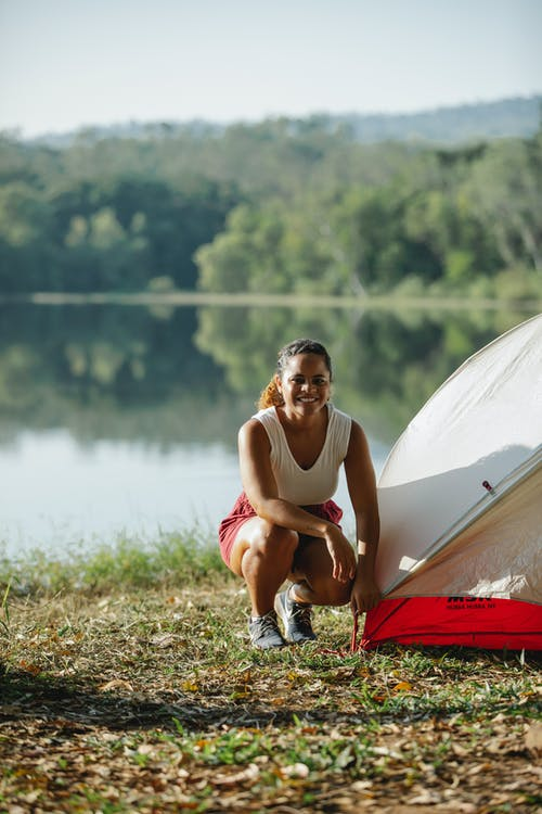 Full body young delighted Hispanic female traveler in casual wear sitting on river bank near tent and looking at camera