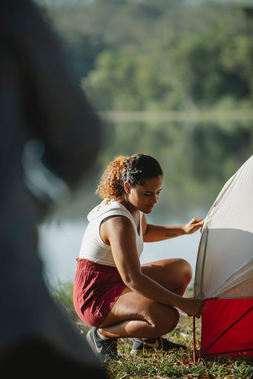Concentrated tourist putting up tent on bank of river