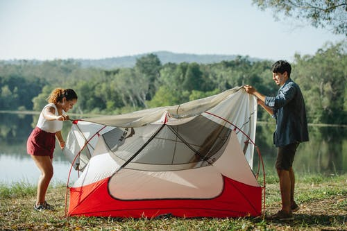 Full body side view of young multiracial couple of travelers putting up colorful tent on river bank covered with grass in summer day