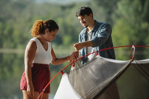 Content multiethnic couple of hikers setting up tent against river during summer journey in sunlight