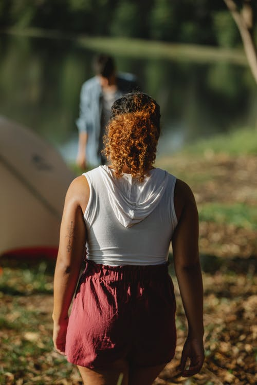 Mujer En Camiseta Blanca Sin Mangas Y Falda Roja De Pie En El Suelo