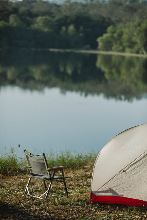 Tent with camping chair on grass against river