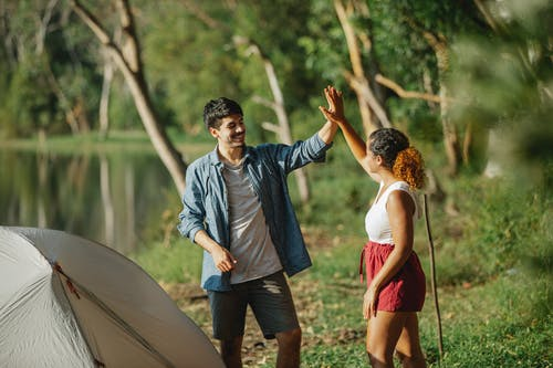 Cheerful male tourist and anonymous ethnic female partner giving high five while looking at each other on river shore near tent