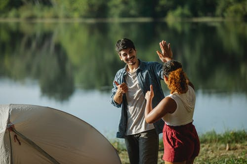 Glad male hiker with unrecognizable ethnic female beloved showing thumbs up and giving high five while looking at each other in campsite