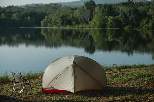 Tent and camping chair on river shore in summer