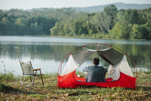 Back view of unrecognizable male tourist admiring lake and lush green trees while sitting in tent on coast