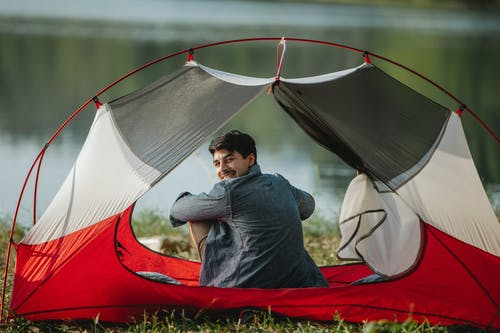 Cheerful male traveler in tent against river