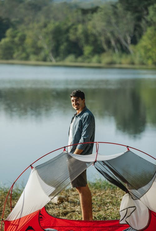 Side view of adult cheerful male traveler looking at camera between tent on shore and lake