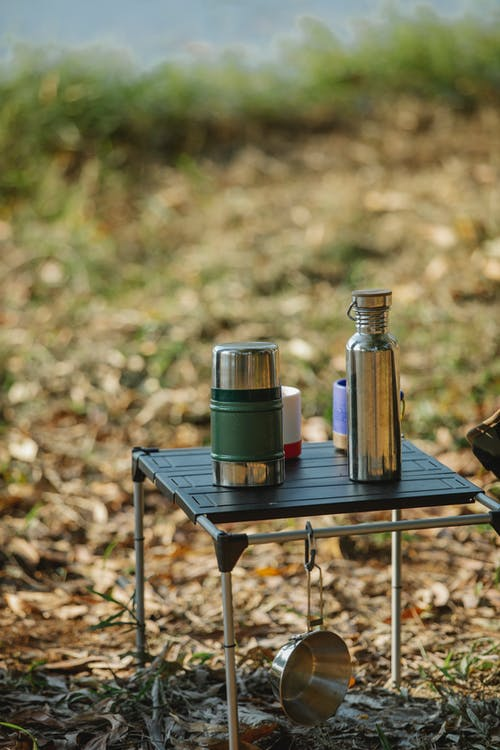 Portable table with vacuum flasks on coast